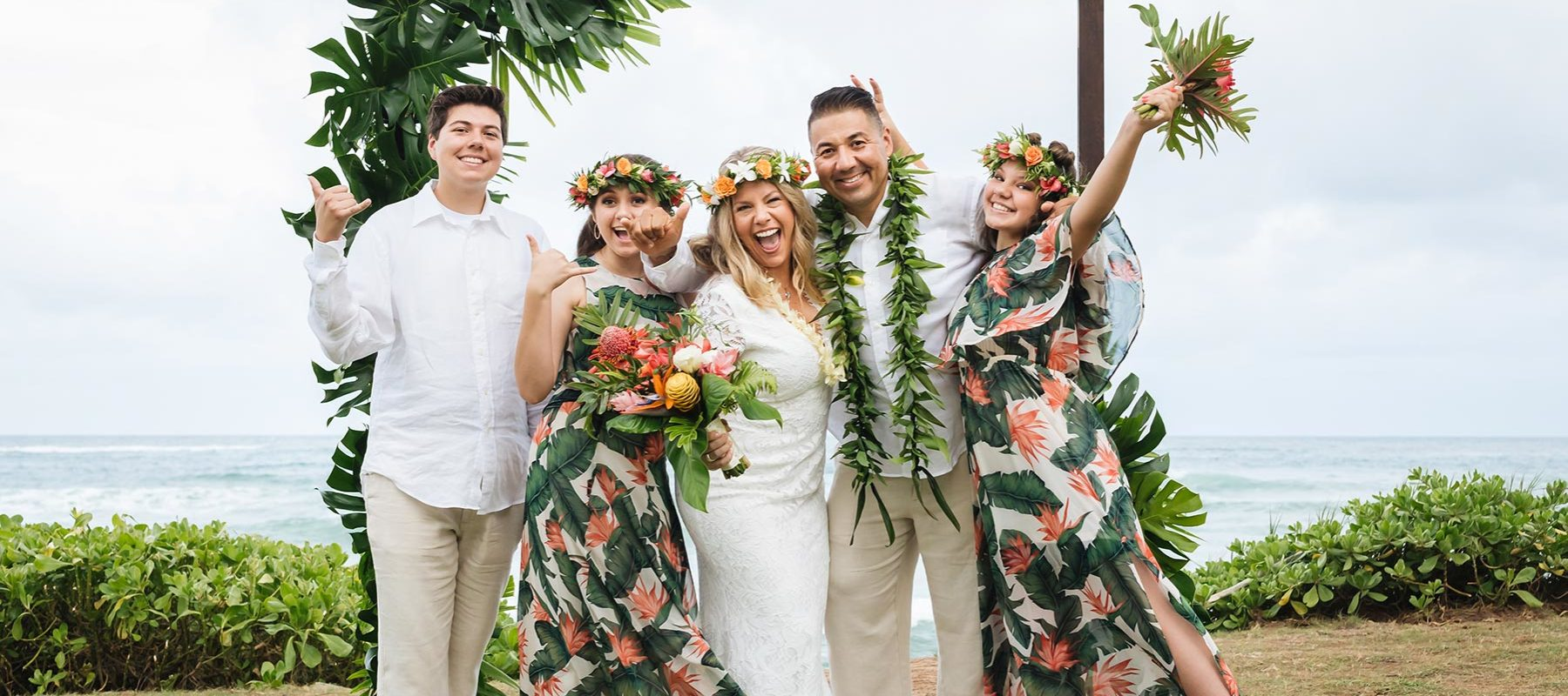 Family celebrating vow renewal on Kauai with arch way and haku leis.