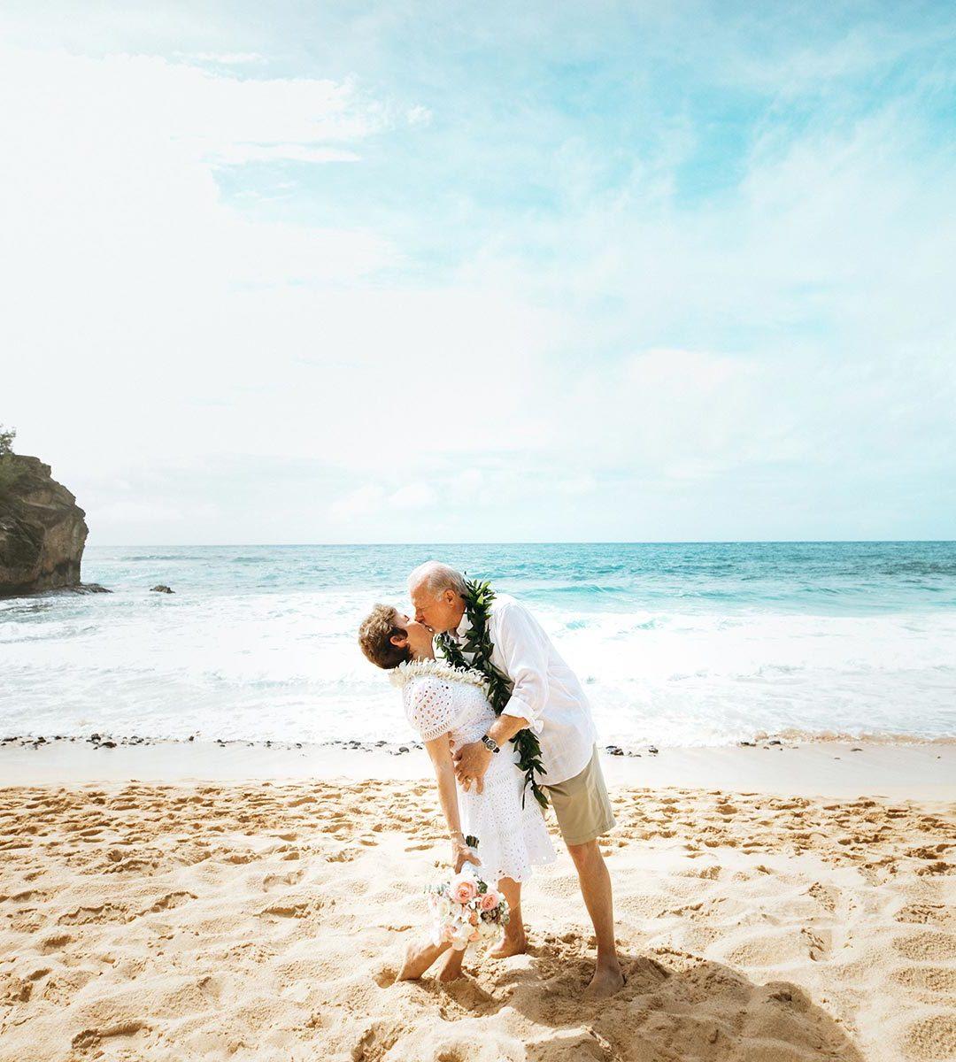 Kissing wife during vow renewal at Shipwrecks beach in Kauai.